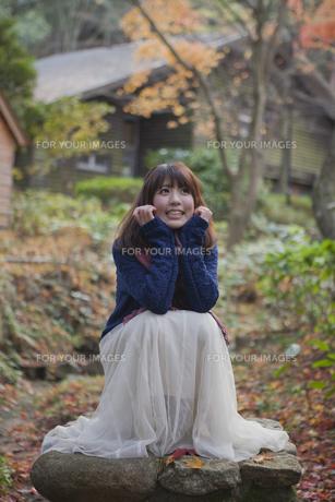 秋の紅葉の公園で座っている笑顔の女性の素材 [FYI01096653]