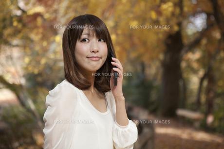 秋の紅葉した公園で立って携帯電話を掛けている女性の素材 [FYI01096654]