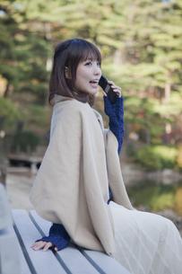 秋の紅葉の公園の池の前のベンチで電話をする女性の素材 [FYI01096660]