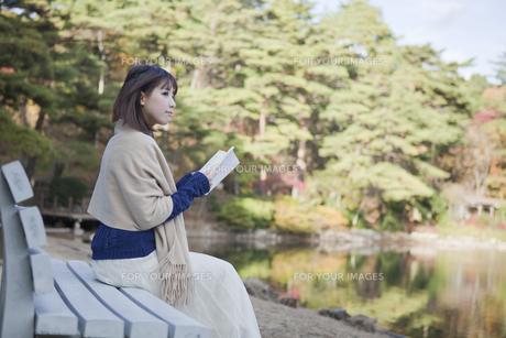 秋の紅葉の公園の池の前のベンチで本を読む女性の素材 [FYI01096664]
