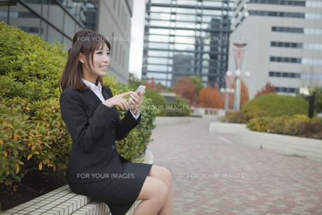オフィス街でメールをするビジネスウーマンの素材 [FYI01096677]