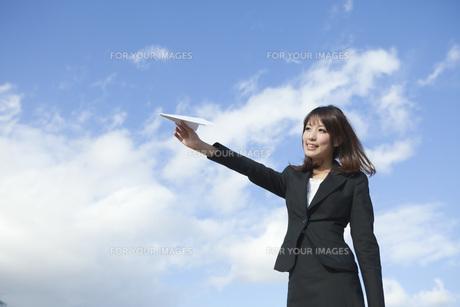 紙飛行機を飛ばすビジネスウーマンの素材 [FYI01096699]