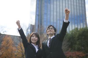 ビルの前でガッツポーズするビジネスウーマンとビジネスマンの素材 [FYI01096701]