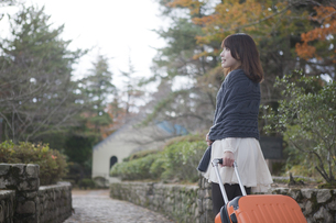 秋の石畳をトランクを引いて歩く笑顔の女性の素材 [FYI01096706]