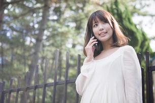 建物の前で笑顔で電話をする女性の素材 [FYI01096715]