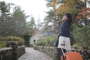 秋の石畳をトランクを引いて歩く笑顔の女性の素材 [FYI01096724]
