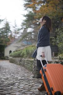 秋の石畳をトランクを引いて歩く笑顔の女性の素材 [FYI01096727]