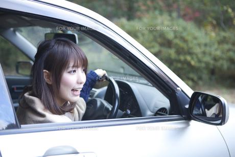 秋の紅葉の公園の駐車場で車の運転をする女性の素材 [FYI01096735]