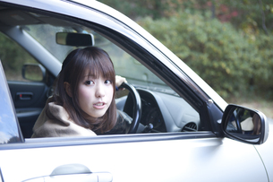 秋の紅葉の公園の駐車場で車の運転をする女性の素材 [FYI01096739]