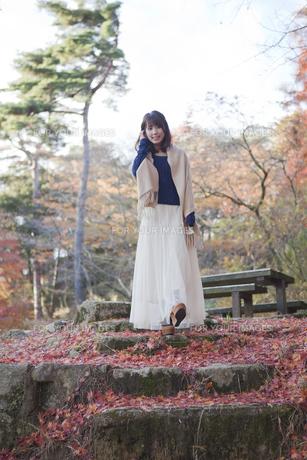 秋の紅葉の落ち葉の上の階段を歩く笑顔の女性の素材 [FYI01096741]