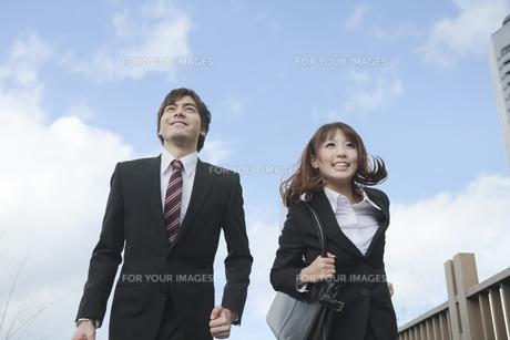 ビルの前を走るビジネスマンとビジネスウーマンの素材 [FYI01096764]