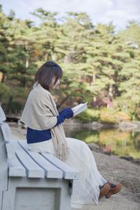 秋の紅葉の公園の池の前のベンチで本を読む女性の素材 [FYI01096780]