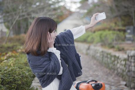 秋の石畳にトランクを置いて写真を撮っている笑顔の女性の素材 [FYI01096797]