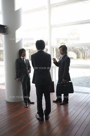 ホールで話しているビジネスマン3人の素材 [FYI01115271]