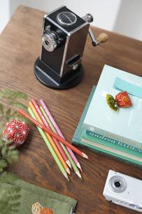 机の上の鉛筆削りと色鉛筆と重ねた本の素材 [FYI01115375]