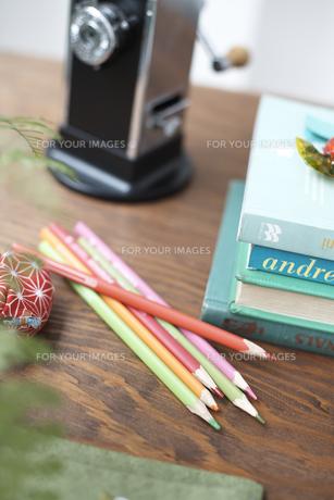 机の上の鉛筆削りと色鉛筆と重ねた本の素材 [FYI01115384]
