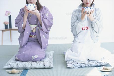 お茶を口元に運ぶ女性2人の素材 [FYI01120022]