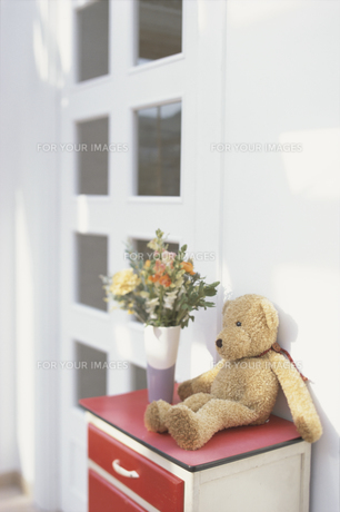 赤いチェストの上の花とテディベアの素材 [FYI01120381]