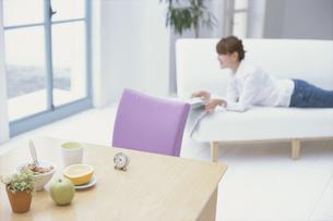 ソファに寝転んで新聞を読む女性の素材 [FYI01120387]