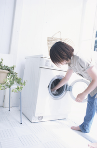 洗濯機に手を入れる女性の素材 [FYI01120556]