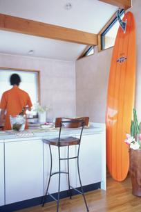 サーフボードのあるキッチンに立つ男性の素材 [FYI01121116]