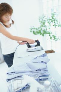 畳んだシャツとアイロン掛けする女性の素材 [FYI01121195]