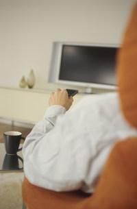 テレビの前でリモコンを持つ男性の手の素材 [FYI01122266]
