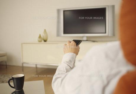 テレビの前でリモコンを持つ男性の手の素材 [FYI01122335]