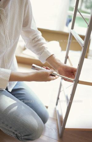 棚のネジを締めている女性の手元の素材 [FYI01122400]