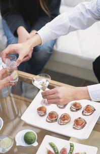 カクテルを持つ手元と皿に盛り付けられたカナッペの素材 [FYI01122522]