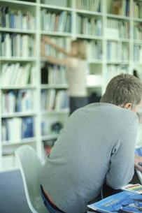 座る男性の後姿と本棚の本を取る女性の素材 [FYI01122861]