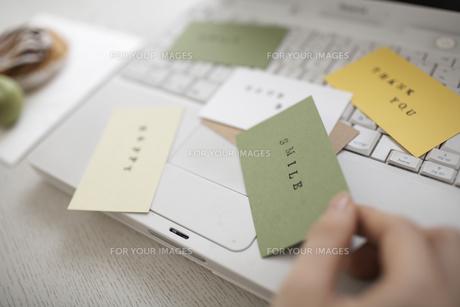 ノートパソコンの上に散らばったカードを持つ手の素材 [FYI01123703]