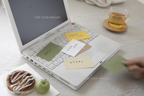 ノートパソコンの上に散らばったカードを持つ手の素材 [FYI01123708]