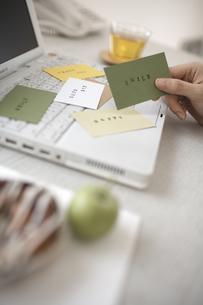 ノートパソコンの上に散らばったカードを持つ手の素材 [FYI01123709]