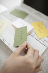 ノートパソコンの上に散らばったカードを持つ手の素材 [FYI01123724]