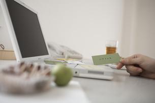 ノートパソコンの上に散らばったカードを持つ手の素材 [FYI01123734]