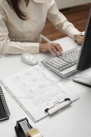 オフィスでパソコンのキーボードを打つ女性の手元の素材 [FYI01123807]