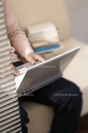 ブラインド越しのソファに座りパソコンをする男性の素材 [FYI01123849]