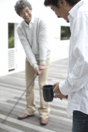マグカップ片手にゴルフを教える男性と習う男性の素材 [FYI01123852]