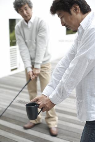 マグカップ片手にゴルフを教える男性と習う男性の素材 [FYI01123854]