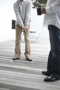マグカップ片手にゴルフを教える男性と習う男性の素材 [FYI01123861]
