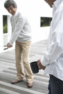 マグカップ片手にゴルフを教える男性と習う男性の素材 [FYI01123866]