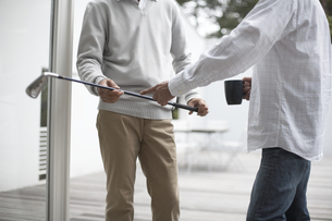 デッキでゴルフクラブやマグカップを持った男性2人の素材 [FYI01123867]