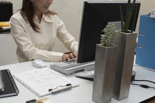 オフィスで笑顔でパソコンに向かう女性の素材 [FYI01123876]