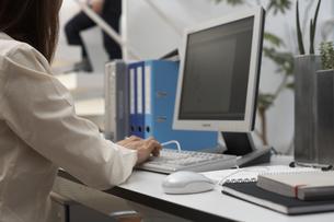 PCに向かう女性と階段を上る男性のシルエットの素材 [FYI01123880]