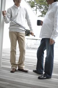 デッキでゴルフクラブやマグカップを持った男性2人の素材 [FYI01123920]