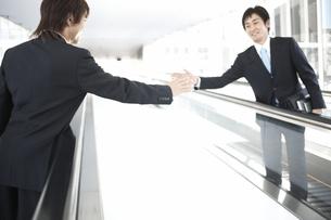 動く歩道で挨拶を交わすビジネスマン2人の素材 [FYI01124047]