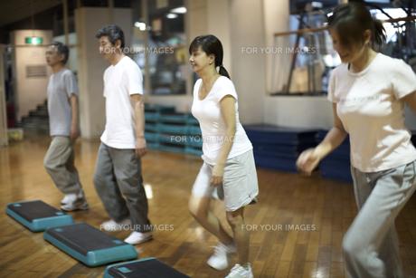 スポーツクラブでステップ運動をする中高年の男女4人の素材 [FYI01124160]