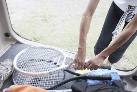 車に積んだテニスラケットを取る女性の素材 [FYI01126483]