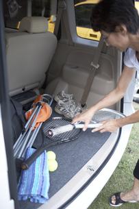 車に積んだテニスラケットを取る女性の素材 [FYI01126578]